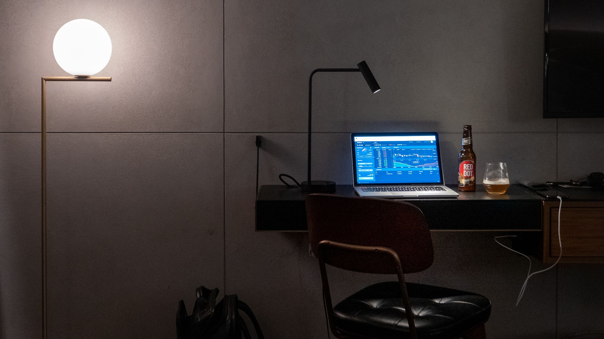 an office desk in the dark with a laptop on it